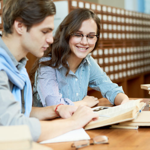 Cheerful content student friends learning from book and knowing new information in preparation for exam in college library